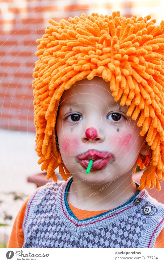 Clown child eating lollipop in a party Dessert Eating Joy Happy Face Make-up Playing Entertainment Feasts & Celebrations Birthday Child Boy (child) Infancy