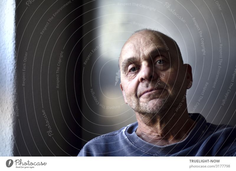 All-natural frontal portrait of a mature man with near-baldness, illuminated by soft, sidelong daylight, looking slightly from above, serious, profound and fearless directly into camera