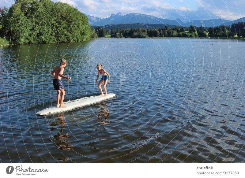 Children play on surfboard in mountain lake Leisure and hobbies Playing Children's game Vacation & Travel Trip Aquatics Swimming & Bathing Surfboard Human being
