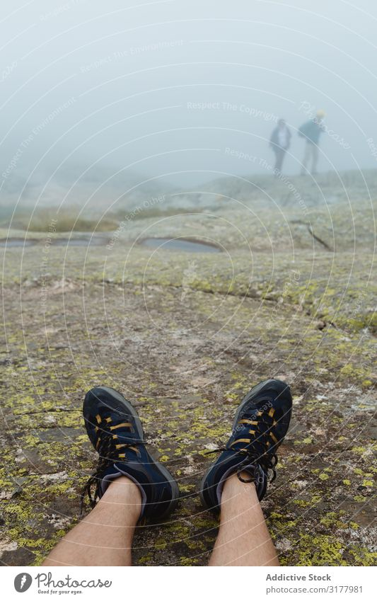 Crop legs on stony ground on misty day Legs traveler Fog Ground Stone Landscape Nature Trip Relaxation Sneakers Hiking trekking Adventure Rock Rough Vague Haze