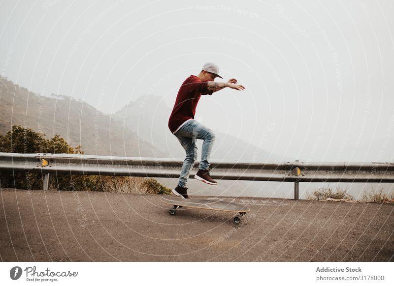 Trendy skateboarder doing trick in nature Man Skateboard Mountain Trick Street Ride Longboard Jump Fog Landscape Remote Panorama (Format) Skateboarding Practice