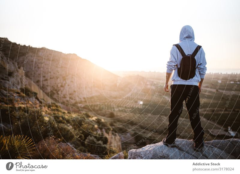 Traveler admiring sunrise in countryside Man Sunrise traveler hiker Valley Morning Landscape Mountain Picturesque achievement Height Sports Wear Stand Stone