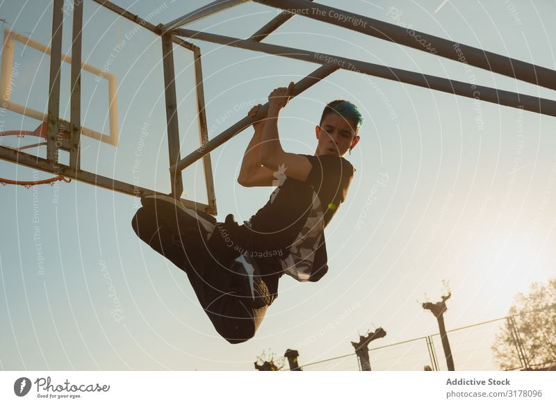 Anonymous teenager hanging behind basketball hoop Youth (Young adults) Basketball Hanging upside down Structures and shapes Sports ground Joy Man Sky