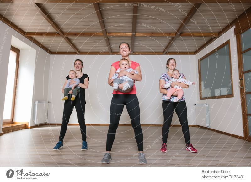 Mothers lifting babies in gym Baby Gymnasium Practice Lift workout Fitness Modern Lifestyle Woman Child Happy Smiling Cheerful Joy Sportswear Group Playing