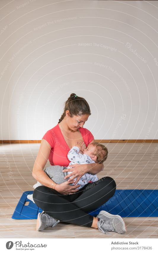 Mother feeding baby in gym Feeding Baby Gymnasium Breasts Fitness Sports Woman workout Child Suck Milk Story Sit Smiling Cheerful Happy Lifestyle