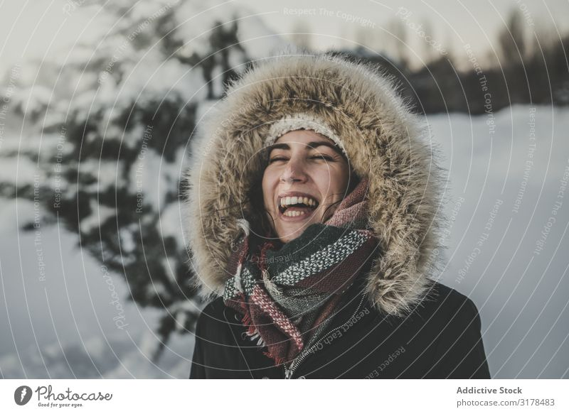 Young woman laughing on snowy background Woman Laughter Joy Snow Attractive Youth (Young adults) Warmth Clothing Fur coat Tree Conifer Winter Happy Happiness