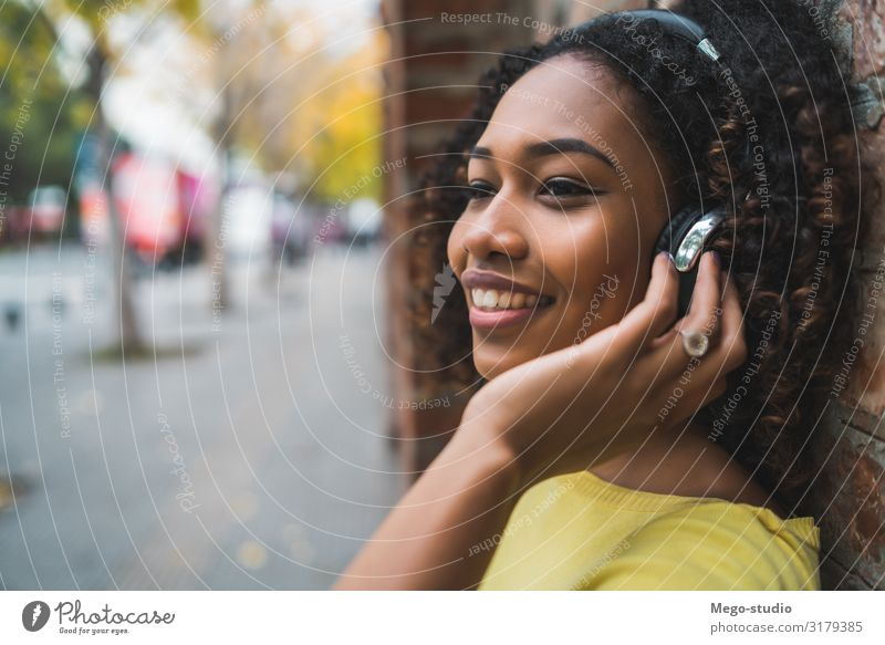Afro american woman listening music Lifestyle Style Joy Relaxation Leisure and hobbies Entertainment Music Woman Adults Street To enjoy Listening Smiling