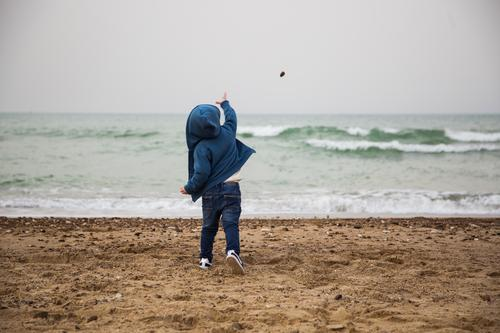 Child throws a stone in the sea Human being Blue Ocean Loneliness Winter Beach Life Autumn Playing Stone Sand Masculine Body Waves Infancy