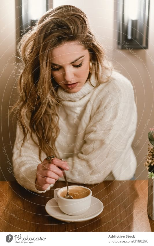 Elegant woman mixing coffee in cafe Woman Café Coffee Stir To enjoy Sit Table