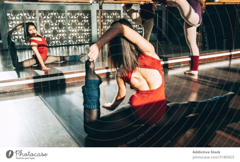 Two concentrated women warming up in sunny class in front of mirror. Woman dancers Stretching Studio shot Practice Sportswear Mirror Partner stretch flexibility