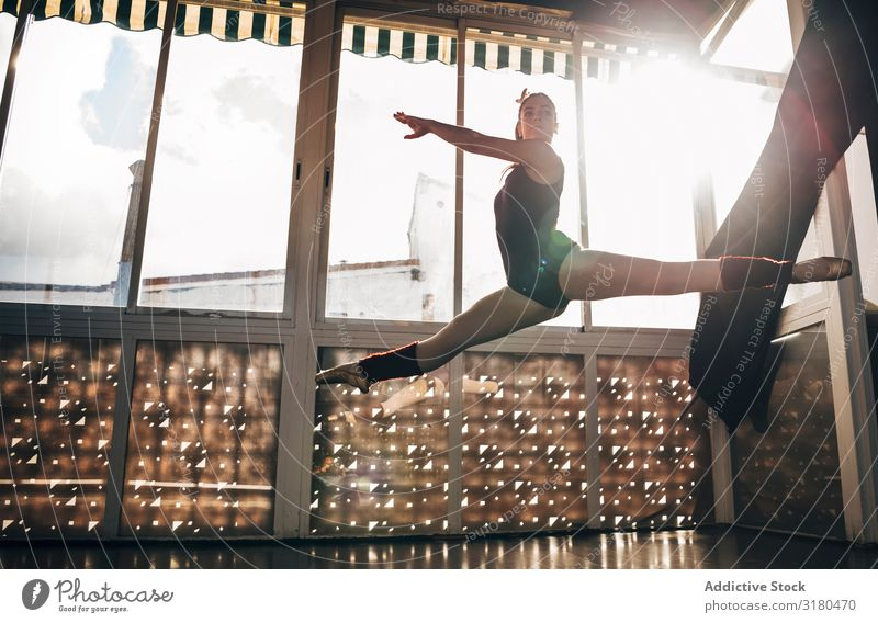 Young slim ballerina jumping above ground in studio flexing legs. Woman Ballerina Jump Splits Ballet pose Movement Acrobatics Gymnastics Dancer