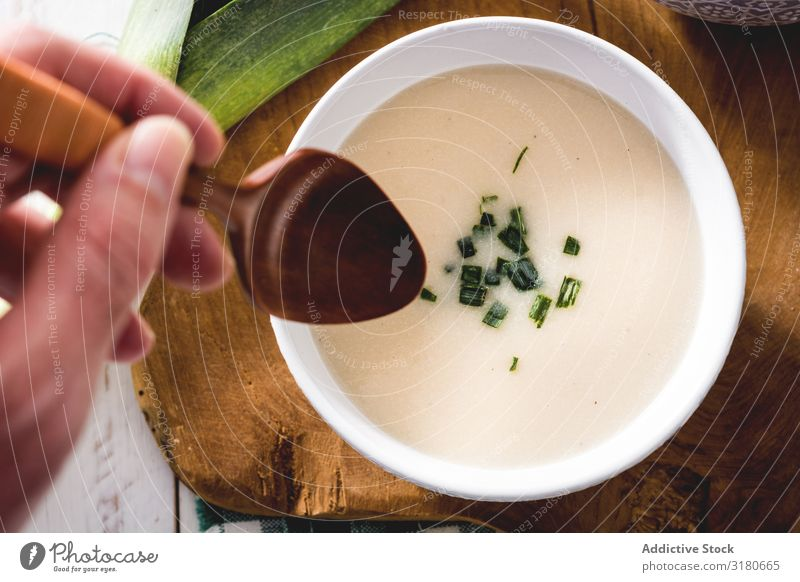 crop hand with spoon and tasty Vichyssoise soup on wooden table with leek Appetizer Bowl Cream Creamy Diet Food French Fresh Gourmet Healthy Home-made Isolated