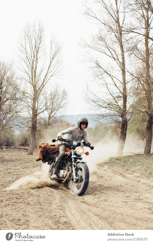 Man riding motorcycle on dusty road Motorcycle Ride Nature Vacation & Travel Tree Leafless Dust Landscape Trip Transport Vehicle Drive Freedom Lifestyle