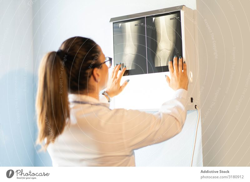 Young doctor with x-ray film document on wall Doctor Medication Radiology Uniform Film Image Wall (building) Room Woman Looking Youth (Young adults) radiography