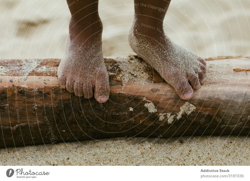 Anonymous black kid walking on log Child Legs Walking Log Sand Summer Beach Barefoot Small Wet Lifestyle Leisure and hobbies Rest Relaxation Black Ethnic