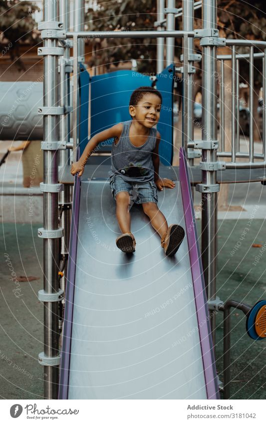 Smiling black boy on slide Boy (child) Playground Slide Looking away Child Joy Leisure and hobbies Lifestyle Rest Relaxation Black African-American Ethnic Park