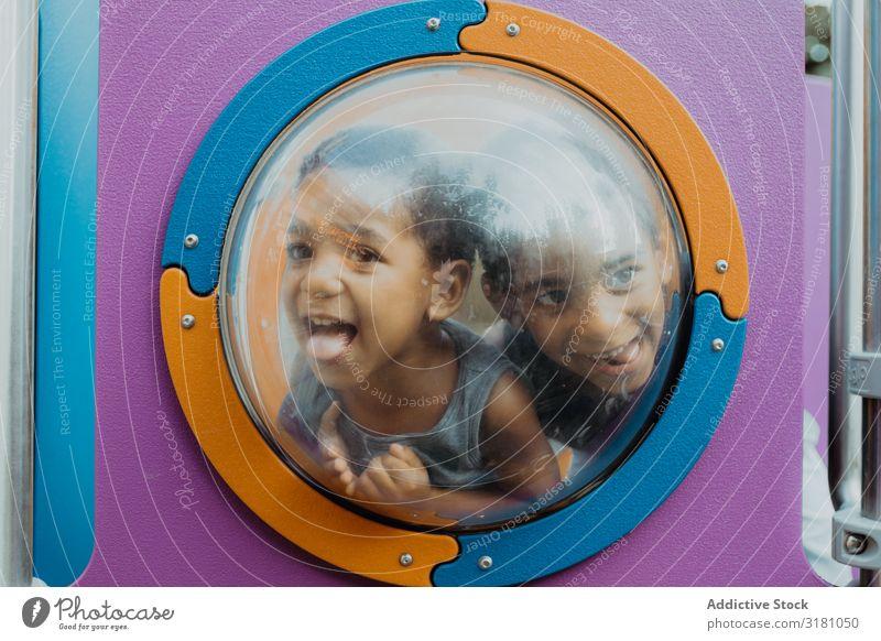 Funny black boys behind porthole on playground Boy (child) Playground Grimace Porthole Happy Action Joy Looking away Child brothers siblings Black Ethnic