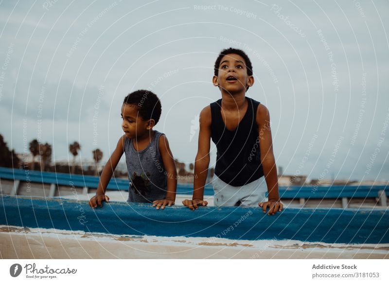 Amazed black boys on boat Boy (child) Watercraft Beach Clouds Sky Black Together Joy Lean Vessel Child siblings brothers African-American Leisure and hobbies
