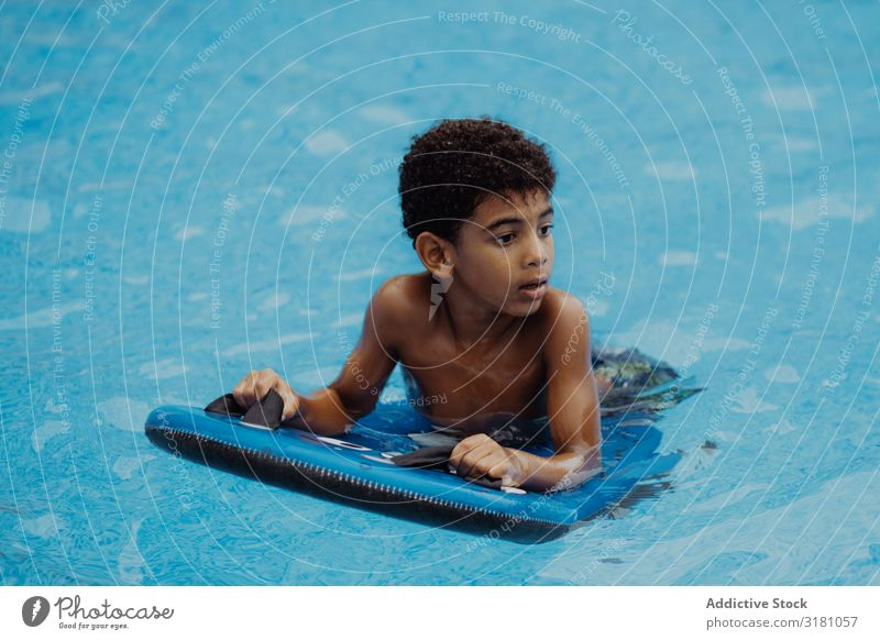 Black boy swimming in pool Boy (child) Swimming pool Looking away Summer Happy Joy Water Vacation & Travel Child African-American Ethnic Inflatable Relaxation