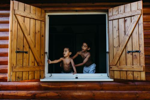 Black boys looking out window brothers Window House (Residential Structure) Wood Open Joy Together African-American Child Boy (child) siblings shirtless Shutter
