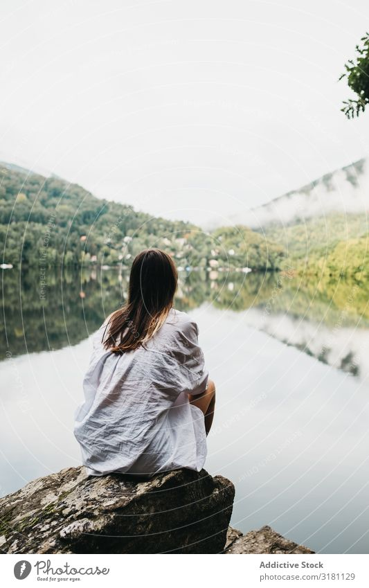 Woman sitting on rock near lake and mountains Sit Rock Lake Mountain Picturesque Water Coast Surface Amazing Vantage point Hill Stone Sky Clouds Glade Summer