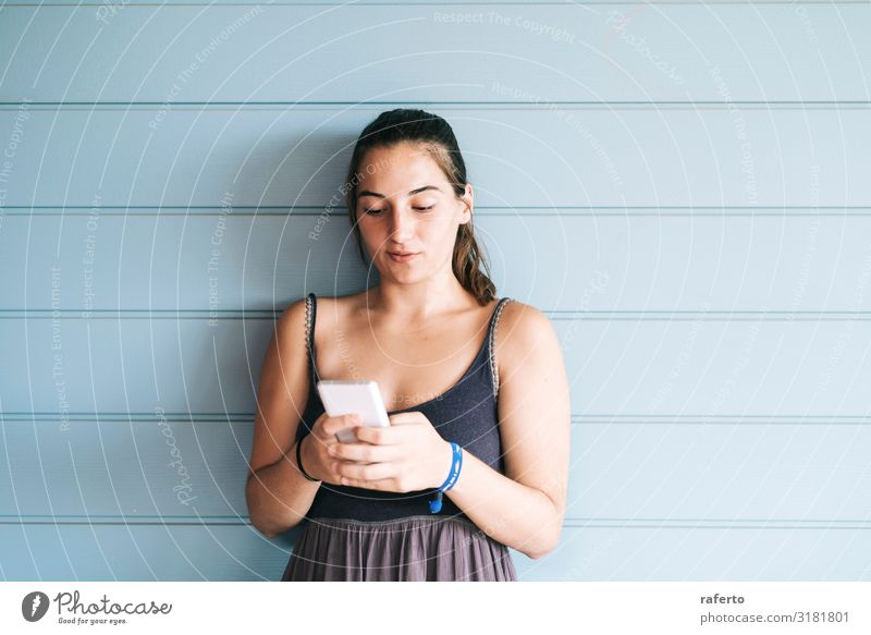 Beautiful young woman leaning on wall using a smartphone Lifestyle Happy Summer Telephone Cellphone PDA Technology Human being Feminine Young woman