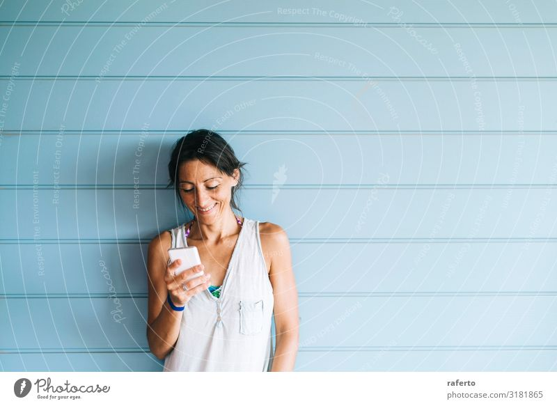 Beautiful woman leaning on wall while using smartphone Lifestyle Happy Summer Telephone Cellphone PDA Technology Human being Feminine Young woman