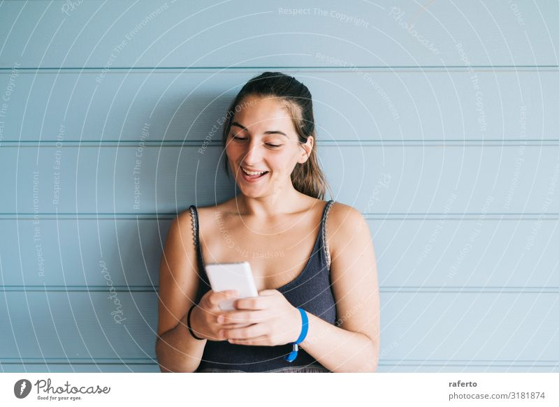 young woman leaning on a wood wall while using a smartphone Lifestyle Happy Beautiful Summer Telephone Cellphone PDA Technology Human being Feminine Young woman