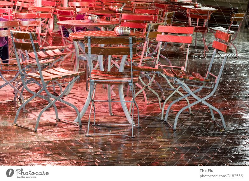 The long wait for guests Beer Wine Rain Downtown Old town Deserted Cobblestones Wait Brown Red Black Silver Table Chair Beer garden Wet Damp Wood Metal