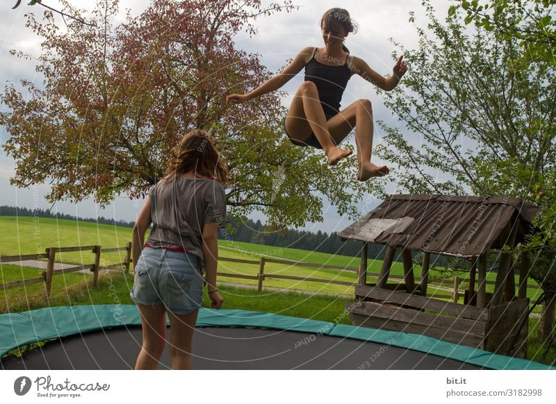 Two girls are jumping on a trampoline together, in nature. One is flying, jumping, the sister is standing to watch, observe, learn. Sports Fitness