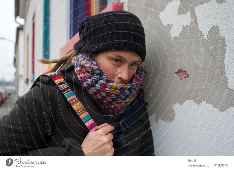 Front view of a young woman with dreadlocks, cap, colourful scarf and bag, who is tired, exhausted, sadly leaning against an old, grey house wall with a colourful window during an excursion in the city, to have a quiet break.