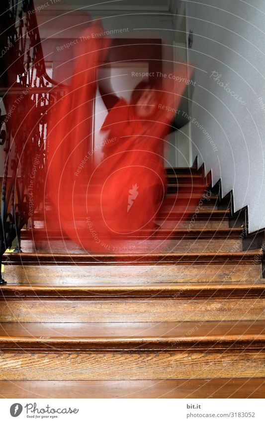 Man waving orange cloth on an old wooden staircase. Surrealistic adult waves with cloth at home in nostalgic staircase. Blurred, disguised, blurred sleepwalker, ghost, ghost with cloth in motion blur.