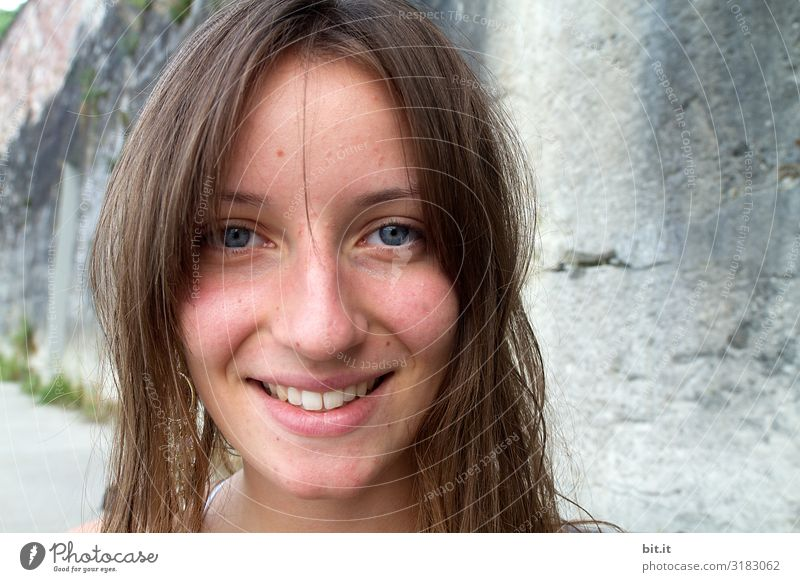 Young woman smiles into the camera, in front of gray wall. Human being Feminine Youth (Young adults) Head Face 0 - 12 months Baby Wall (barrier) Wall (building)
