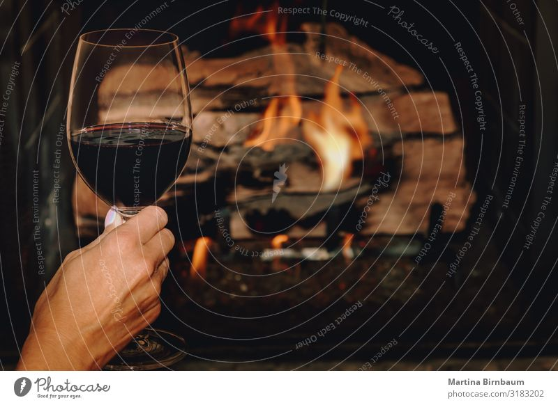 A glass of red wine in front of a burning fire place Alcoholic drinks Lifestyle Relaxation Leisure and hobbies Winter House (Residential Structure)