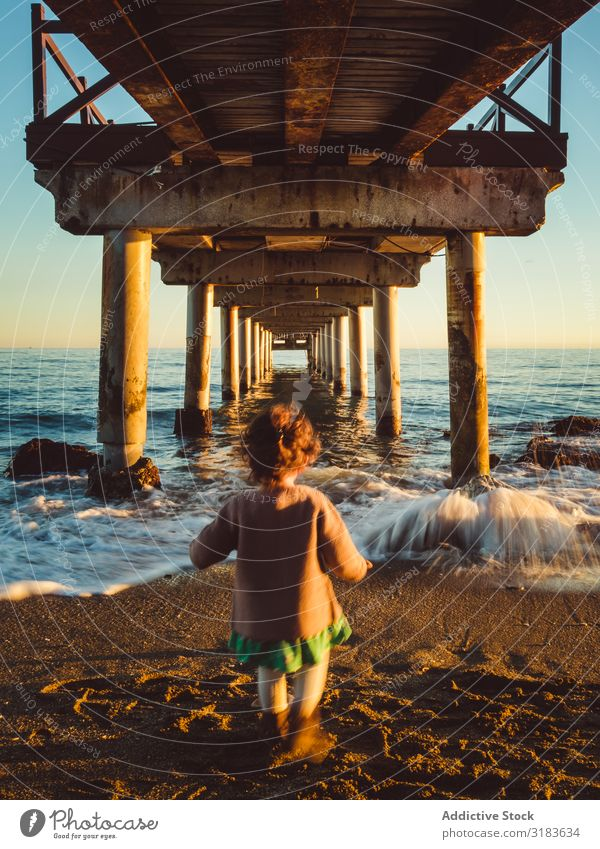 back view of kid under a pier Rear view Girl Child Walking Jetty Sunset Nature Ocean Beach Background picture Sky Water Vacation & Travel Landscape Blue peer