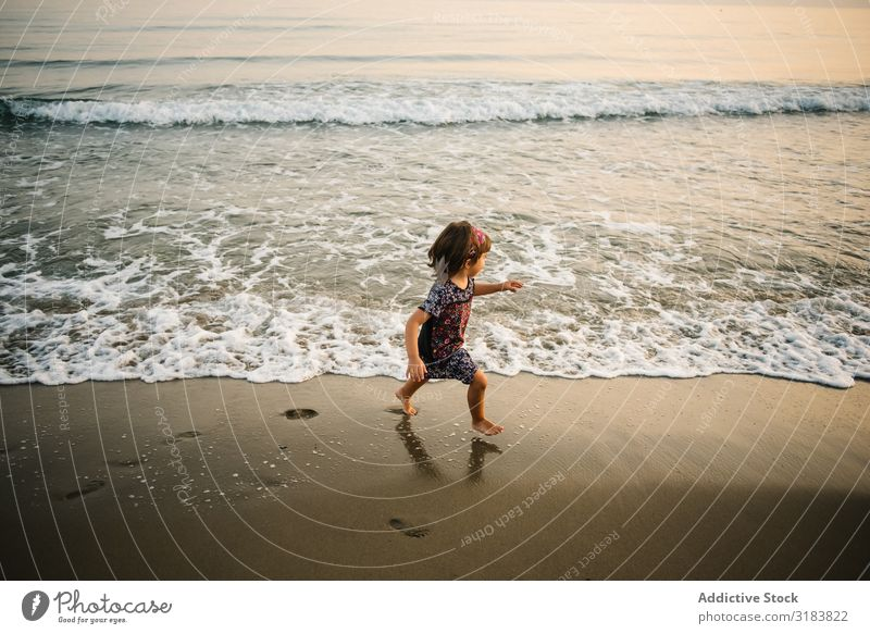 Child going in sea on coast Ocean Coast Girl Water Foam Sand Splash Funny Going Beach Joy Happiness Summer Nature Leisure and hobbies Action Swimming Playing