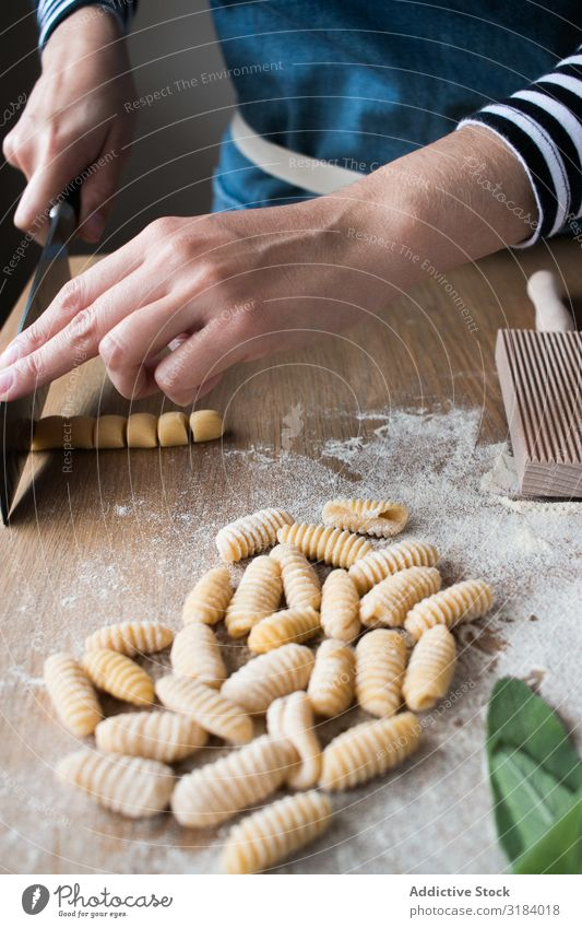 Crop woman making gnocchetti pasta Woman Pasta cutting Dough Preparation Italian Table Kitchen Home-made Tradition Raw Food Cooking recipe Ingredients Fresh