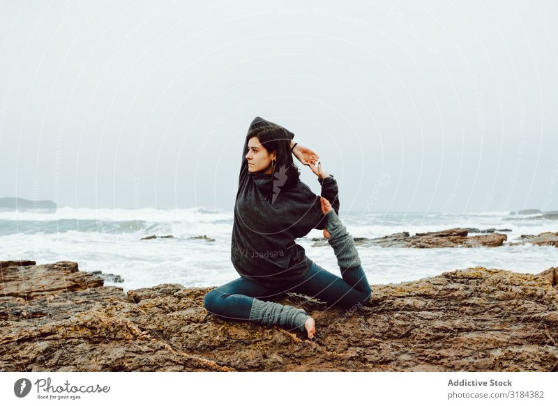 Woman on stones near sea practicing Yoga Ocean Mountain Stone meditating upped hands Rock Water Hill Speed Stream Splash Energy Youth (Young adults) Nature