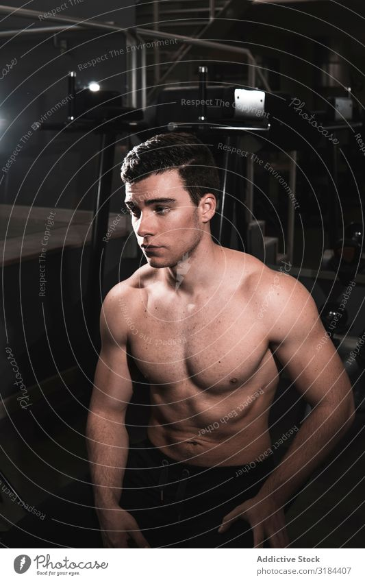 young fitness man resting in the gym Healthy Muscular Fitness Gymnasium Resting Power physical Bodybuilder Athlete Athletic workout Body building Beautiful