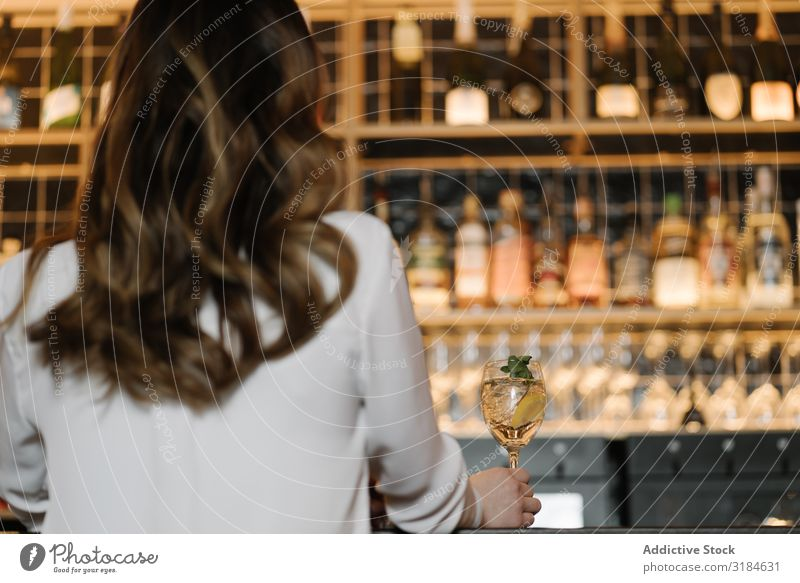 Back view of anonymous woman holding a cocktail in bar Woman Anonymous Cocktail Bar Restaurant Cozy Party Alcoholic drinks Night Feasts & Celebrations Lifestyle
