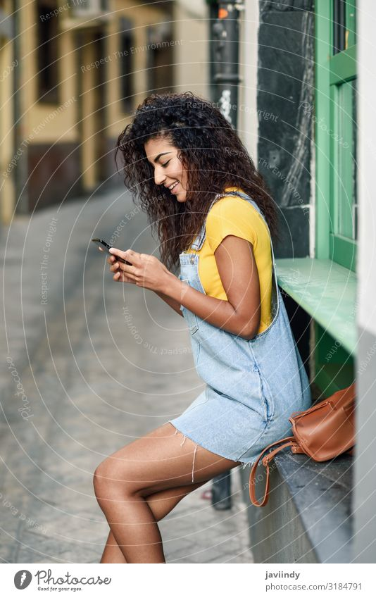 Young Arab girl looking at her smart phone outdoors Lifestyle Style Happy Beautiful Hair and hairstyles Telephone PDA Technology Human being Feminine