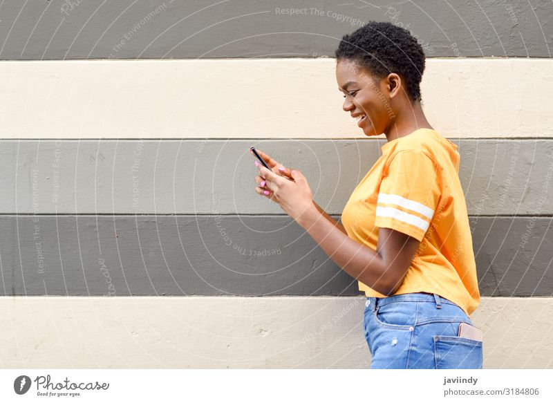 Young black woman laughing using her smart phone outdoors Lifestyle Style Joy Happy Hair and hairstyles Telephone Cellphone PDA Technology Internet Human being