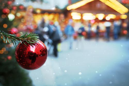 Blurred l red, shiny Christmas tree ball, hanging on fir branch in green, on illuminated Christmas market. Christmas mood with Christmas tree on Christmas market, illuminated with a lot of light, in the twilight. Evening mood on Christmas market with jewellery
