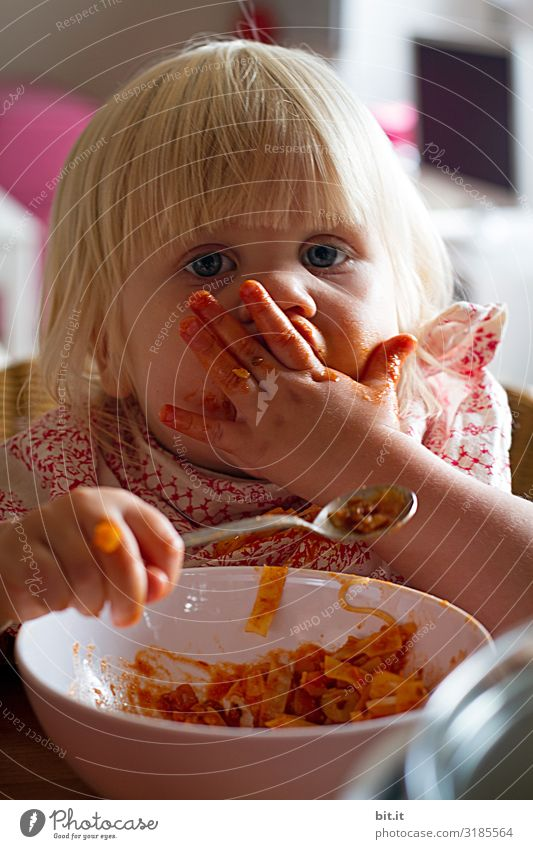 Little blonde sweet girl is noodles with tomato sauce and smears her face with red sauce with her hand, she holds the small spoon in her hand, over a bowl and looks curiously into the camera, at home in the apartment.