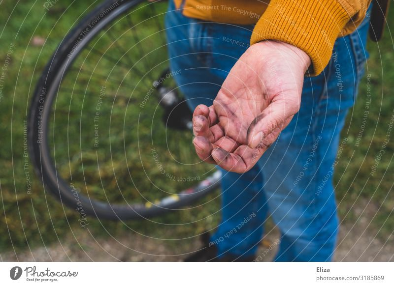 A man has dirty hands after fixing his bike Cycling Dirty Repair Bicycle tyre by hand oil bicycle repair Man Flat tire Litterbug Colour photo Exterior shot Day