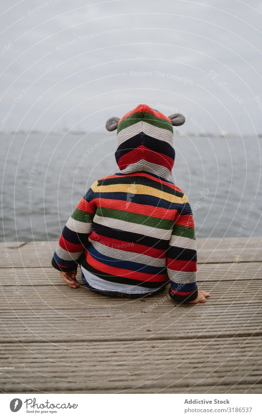 Anonymous kid sitting on pier Child Jetty Ocean Sit Baby Easygoing Lifestyle Leisure and hobbies Rest Relaxation Striped Jacket Car Hood marine Water Coast