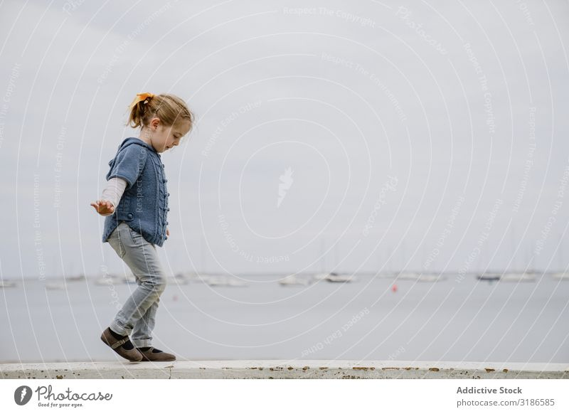 Girl balancing on border near sea Border Balance Walking Ocean Coast outstretched arms Small Lifestyle Leisure and hobbies Child Easygoing Water Beach Dull