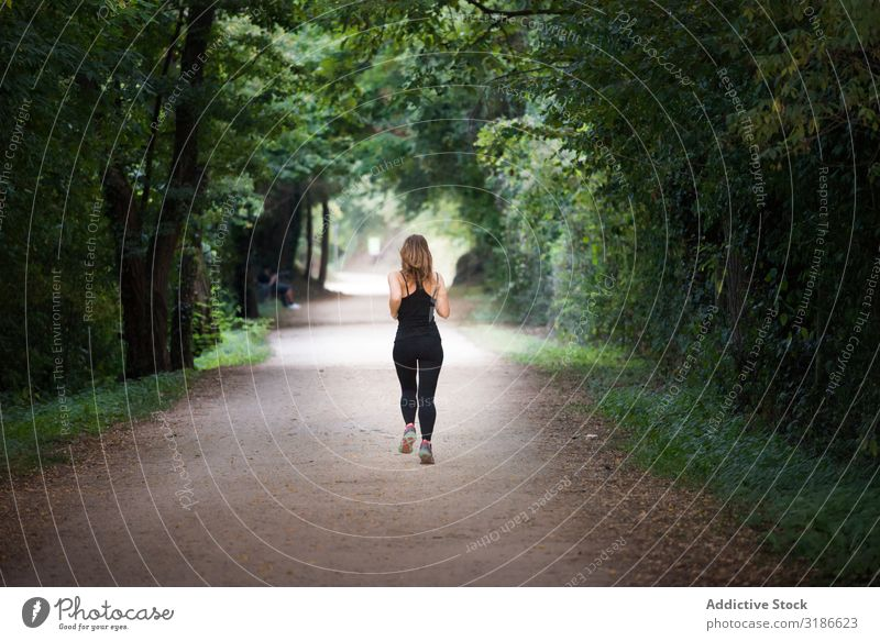 young fit woman running away doing sport on a path in park Woman Running Park Fitness Jogging Lifestyle Sports Healthy Youth (Young adults) pretty Human being