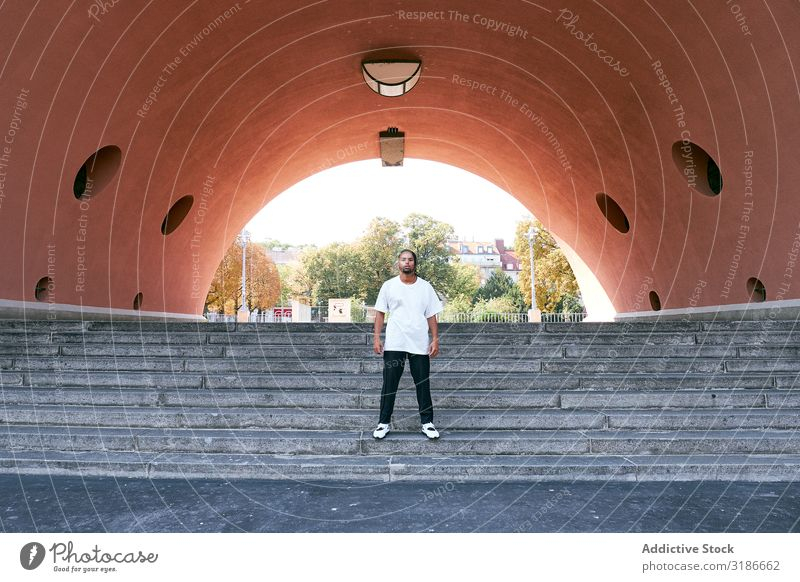 Trendy black guy posing near modern arch Man Arch Street Modern Looking into the camera African-American Fashion fashionable Self-confident Youth (Young adults)