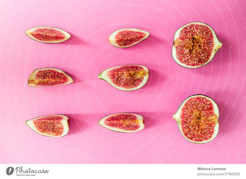Ripe figs cut on a pink background. Minimal flat lay. Fruit Nutrition Diet Exotic Autumn Fresh Pink Red Raw Half Fig Seasons Cut sweet Slice Vegan diet healthy